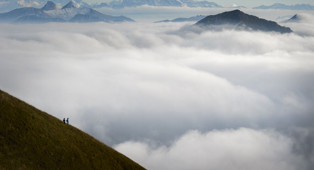 Tourists face a sea of mist engulfing the Alpes from the Moleson peak, Western Switzerland on September 26, 2015