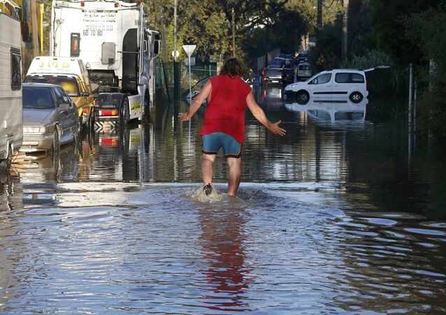 A man reacts as he wades through flood waters near cars after flooding caused by torrential rain in Biot, France