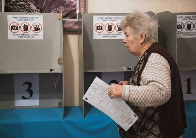 A woman during voting at a ballot station in Bishkek where elections to Kyrgyzstan's one-house parliament are taking place
