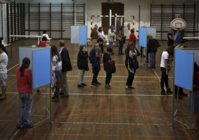People vote at a polling station during the general election in Lisbon, Portugal October 4, 2015.