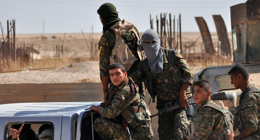 Fighters from the Kurdish People's Protection Units (YPG) sit in the back of a vehicle in the al-Zohour neighbourhood of northeastern Syrian city of Hasakeh on August 2, 2015, a week after Syrian troops and Kurdish fighters ousted the Islamic State group from Hasakeh