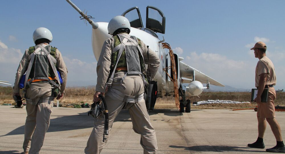 Russian pilots near a Su-24 aircraft before a mission, at the Khmeimim airbase in Syria