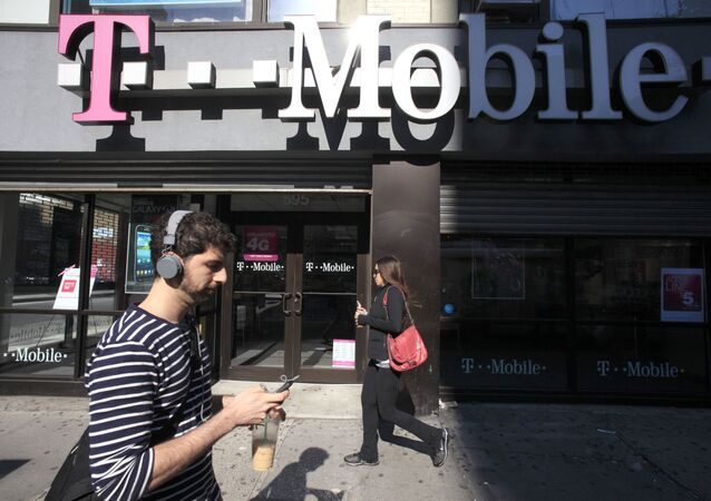In this Sept. 12, 2012 file photo, a man uses a cellphone as he passes a T-Mobile store in New York.