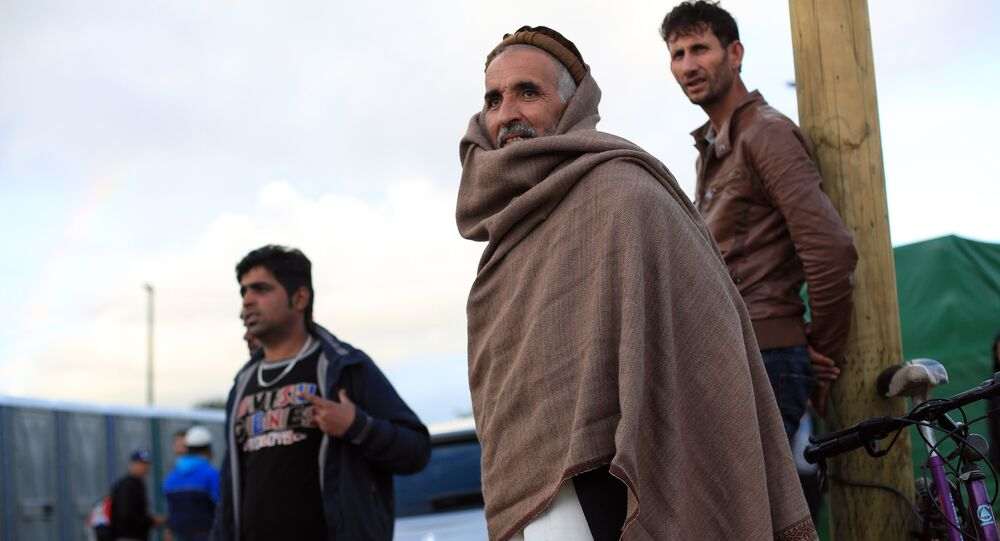 Afghan migrants stand in the Jungle of Calais, northern France, Friday, Sept. 18, 2015.