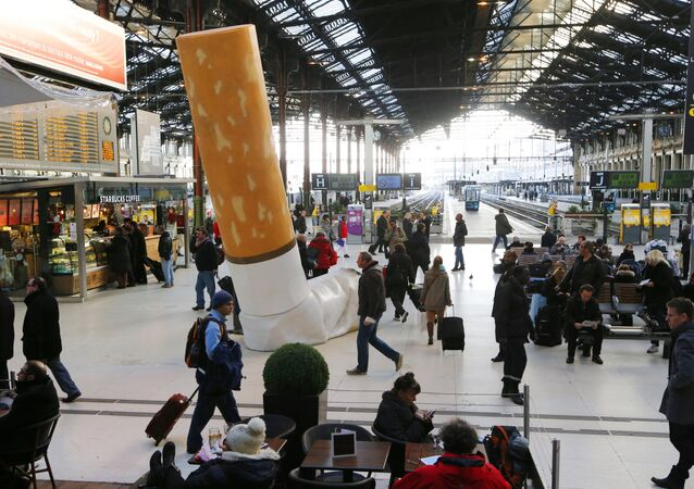 People pass by a giant mock-up discarded cigarette displayed on the ground at the Gare de Lyon railway station in Paris, on December 4, 2012.