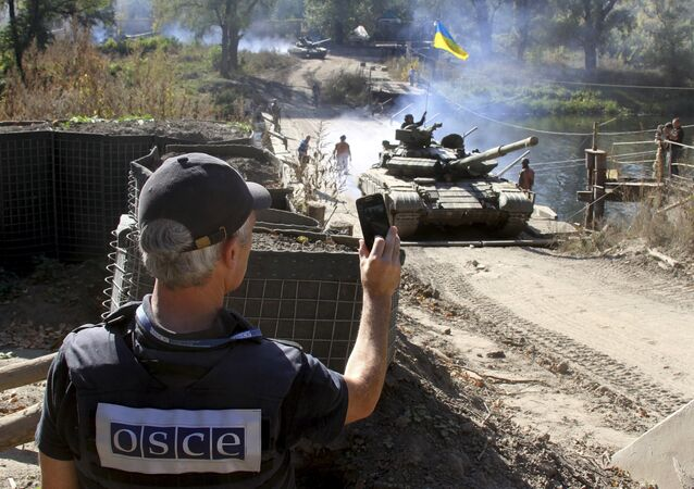 A member of the Organization for Security and Co-operation in Europe (OSCE) monitors the withdrawal of tanks of the Ukrainian armed forces near the village of Nyzhnje in Luhansk region, Ukraine, October 5, 2015