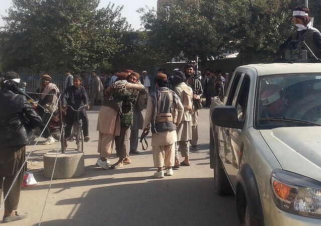 Taliban fighters hug each other a day after they overran the strategic northern city of Kunduz, on September 29, 2015