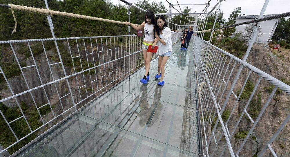 Tourists look down as they walk on a glass suspension bridge at the Shiniuzhai National Geo-park in Pinging county, Hunan province, China, September 24, 2015