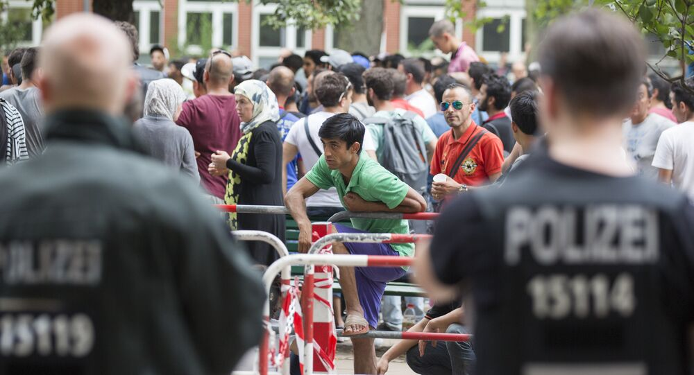 Police stand next to asylum seekers waiting in front of the reception center for refugees in Berlin, Germany, Friday, Aug. 7, 2015.