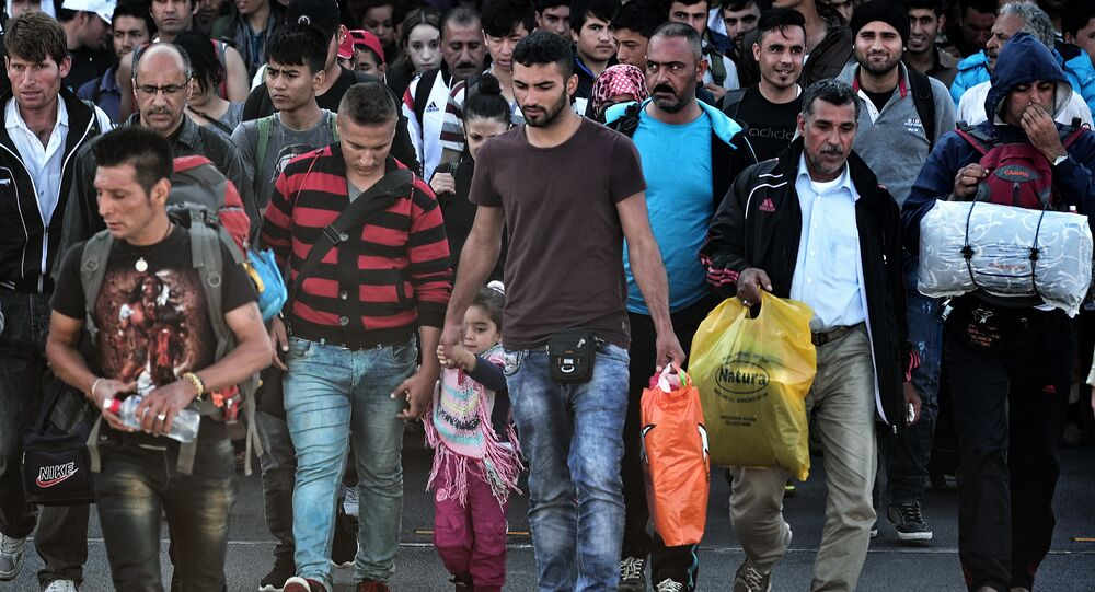Refugees and migrants disembark from a ferry