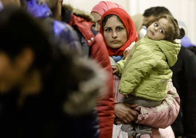 A migrant woman with a child stands in a queue of refugees and migrants after she arrived with a train at the train station Schoenefeld near, Berlin, Germany, Wednesday, Oct. 7, 2015.
