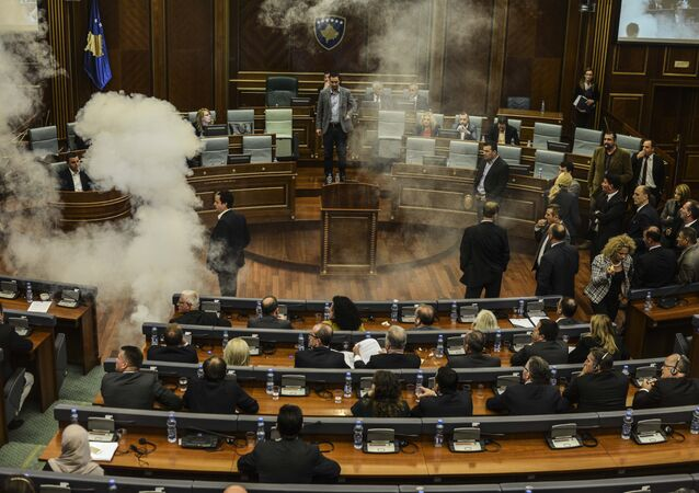 A white cloud of tear gas ascends after being released by opposition lawmakers in Kosovo's parliament in Pristina, on October 8, 2015 causing two MPs to faint, in protest at a recent EU-brokered deal reached by the government with Serbia