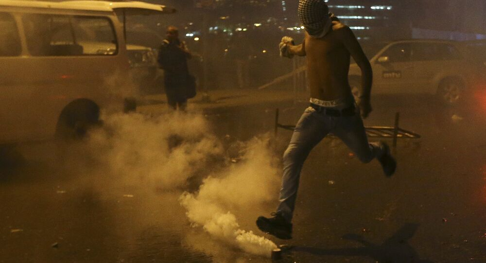 A Lebanese anti-government protester kicks back a tear gas canister shot by security forces during a protest against the ongoing trash crisis and government corruption, in downtown Beirut, Lebanon, Thursday, Oct. 8, 2015. Lebanese security forces used water cannons and eventually fired tear gas canisters to disperse dozens of anti-government protesters who tried to get past security barricades and reach parliament.