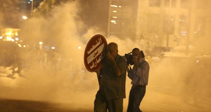 A protester and a cameraman (R) cover their faces as they are affected by tear gas fired by security forces in Martyr square, downtown Beirut, Lebanon October 8, 2015. Lebanese security forces fired tear gas and water cannons to break up an anti-government protest in Beirut on Thursday, and the country's fractious leaders postponed talks aimed at resolving a political crisis that is feeding public discontent.