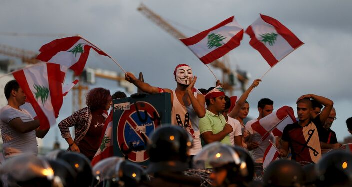 Protesters chant slogans as riot policemen block a street leading to the parliament building during a protest against perceived government failures, including a rubbish disposal crisis, in downtown Beirut, Lebanon October 8, 2015.