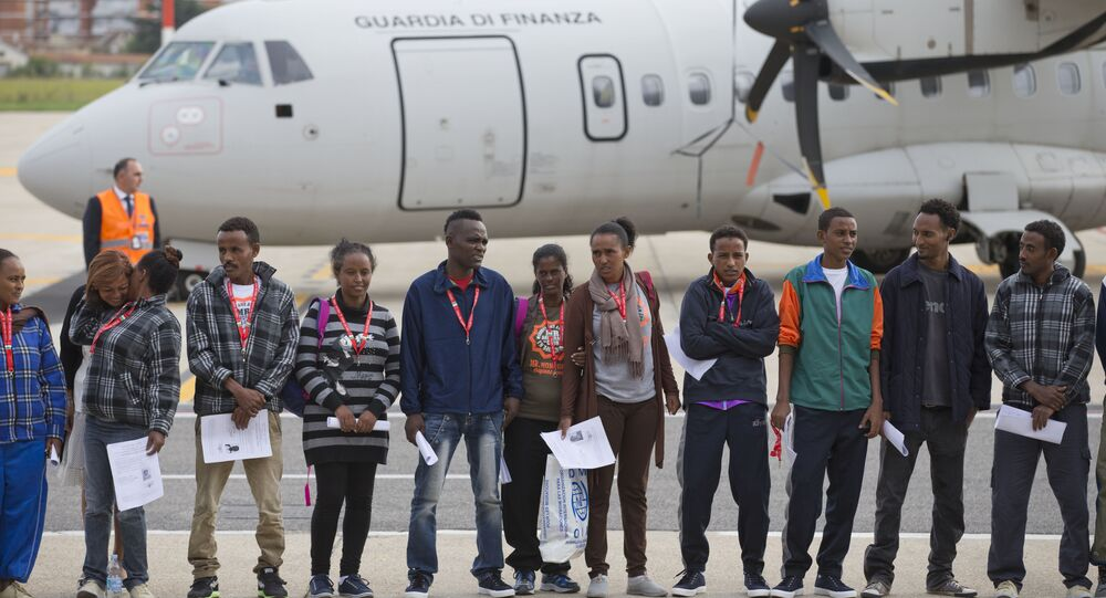 Eritrean refugee pose for a group photo in front of an Italian Financial police aircraft which will take them to Sweden, at Rome's Ciampino airport, Friday, Oct. 9, 2015.