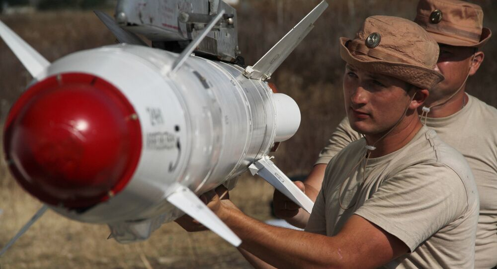 Russian servicemen attach a Kh-25 high-precision missile to a Su-24 aircraft at the Khmeimim airbase in Syria.