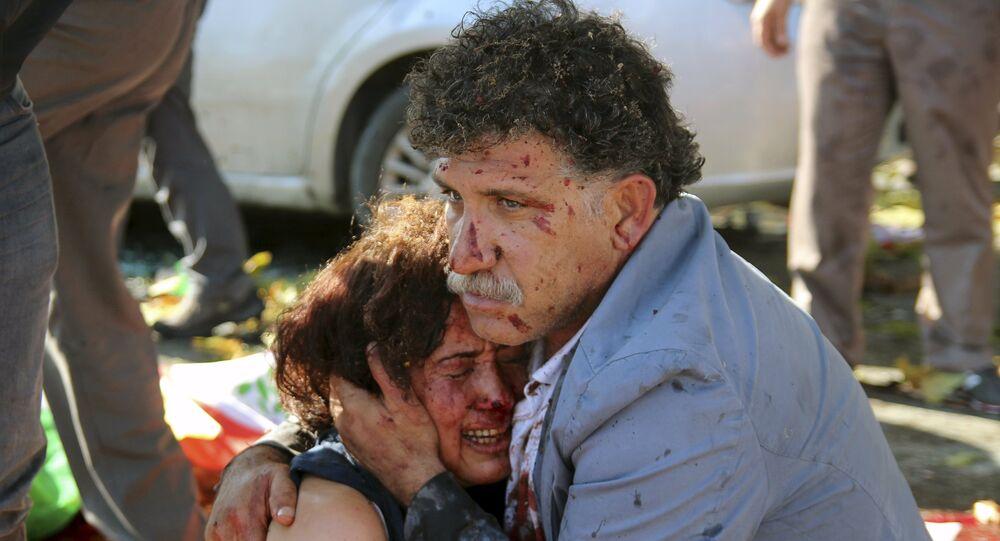 An injured man hugs an injured woman after an explosion during a peace march in Ankara, Turkey, October 10, 2015