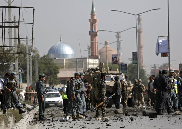 Afghan security personnel keep watch at the site of a suicide car bomb blast in Kabul, Afghanistan October 11, 2015