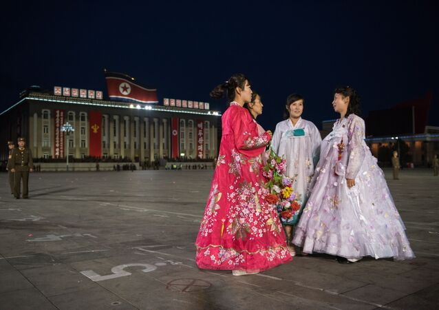 North Korean women wearing traditional 'hanbok' dresses stand on Kim Il-Sung square in Pyongyang on October 10, 2015