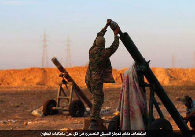 In this image posted on Thursday, Oct. 8, 2015, by the Rased News Network, a Facebook page affiliated with Islamic State, shows Islamic State militants preparing to fire a mortar to shell towards Syrian government forces positions at Tal Arn in Aleppo province, Syria