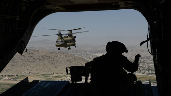 This photo taken on august 11, 2014 shows a US soldier, part of the NATO-led International Security Assistance Force (ISAF), manning a machine gun onboard a Chinook helicopter over the Gardez district of Paktia province - Sputnik International