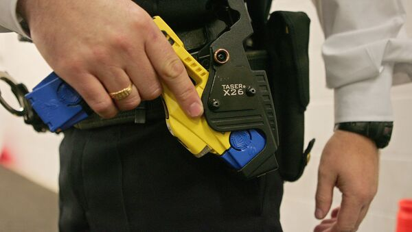 A file photo taken 05 December 2007 shows a British police officer holding a taser gun during a training session at the Metropolitan Police Specialist Training Centre, in Gravesend, Kent, in southeast England - Sputnik International