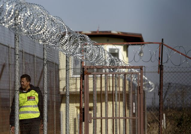 A security guard walks along a fence topped with barbed and razor wire in a facility for a detention of foreigners in the village of Drahonice, western Czech Republic, October 2, 2015. The Refugee Facilities Administration of the Interior Ministry will open this detention centre on October 5, 2015, to house incoming migrants.