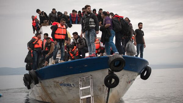 Migrants and refugees are seen aboard a Turkish fishing boat as they arrive on the Greek island of Lesbos after crossing a part of the Aegean Sea from theTurkish coast to Lesbos October 11, 2015 - Sputnik International