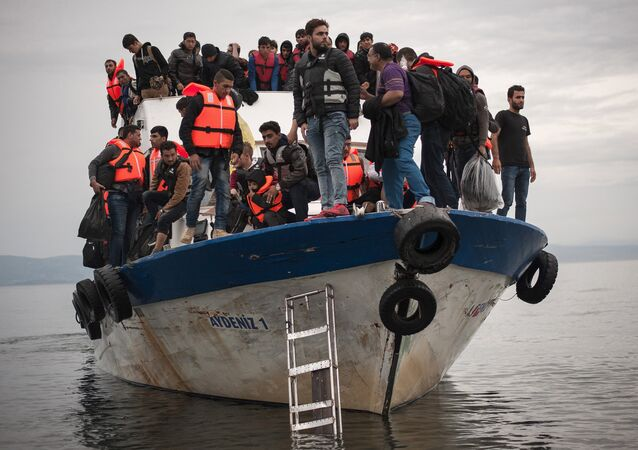 Migrants and refugees are seen aboard a Turkish fishing boat as they arrive on the Greek island of Lesbos after crossing a part of the Aegean Sea from theTurkish coast to Lesbos October 11, 2015