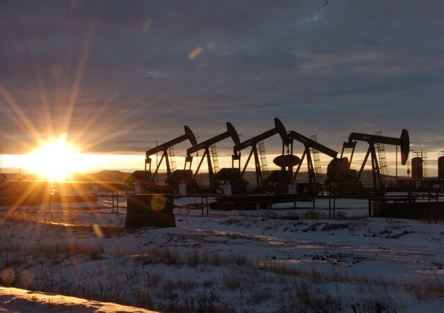 In this Jan. 14, 2015 file photo, some of the 60 rigs that are drilling surrounding McKenzie County, 40 percent of the rigs statewide, work in western North Dakota