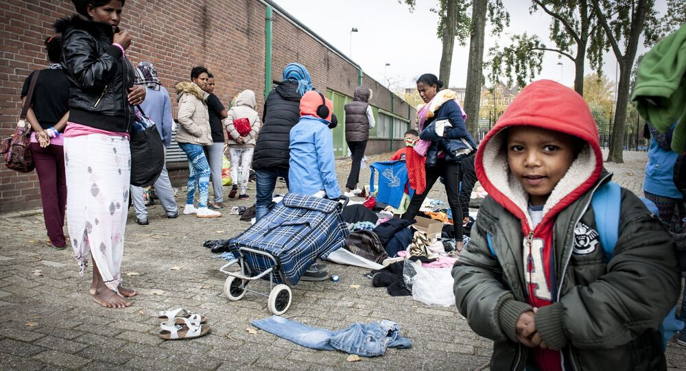 Refugees collect clothes, brought by residents of the neighborhood, outside the Schuttersveld Sports Centre designed as emergency shelter in Rotterdam, The Netherlands, on October 9, 2015