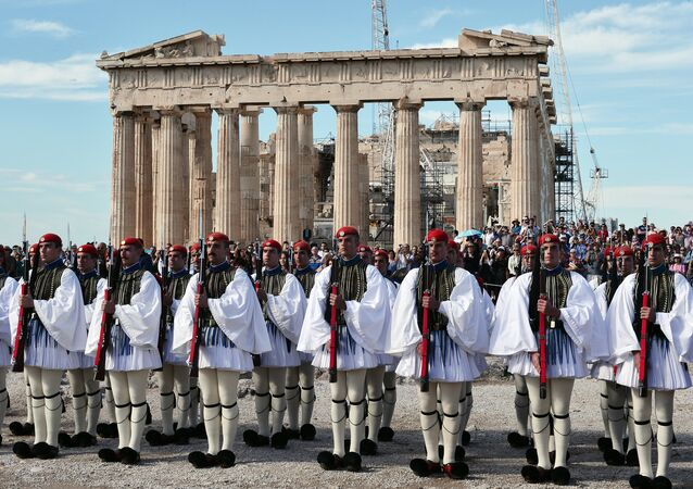 Greek Evzoni presidental guards attend the hoisting of the Greek flag ceremony atop the ancient Acropolis on October 12, 2015, marking the anniversary of the liberation of Athens from the German Nazi occupation in 1944.