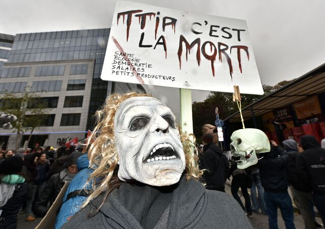 A protester with a mask demonstrates against the free trade agreement TTIP (Transatlantic Trade and Investment Partnership) during an EU summit in Brussels, Belgium on Thursday, Oct. 15, 2015.