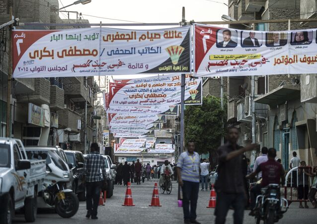 Egyptians walk under campaign banners ahead of the parliamentary elections on September 29, 2015 in the city of Qena, some 650 km (400 miles) south of Cairo