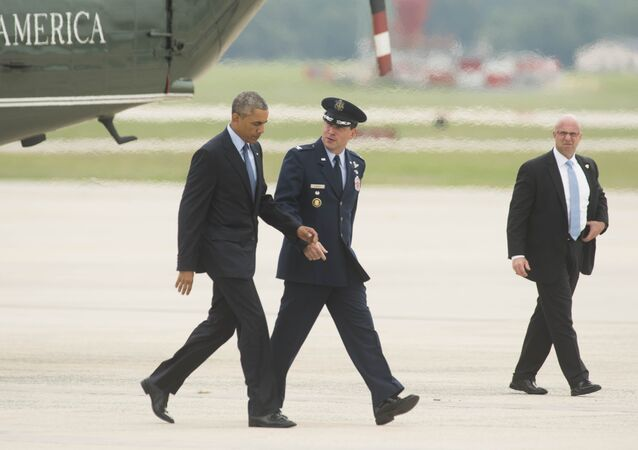 President Barack Obama talks with Col. Dave Siegrist, right, as they walk to Air Force One.