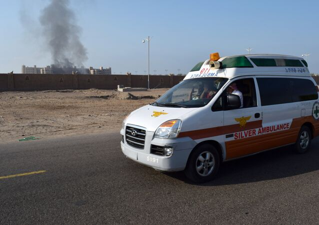 A picture taken on October 6, 2015 shows an ambulance driving as smoke billows from the Al-Qasr hotel in Aden.