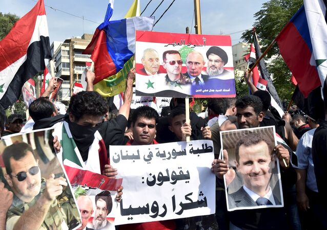 Syrians, living in Lebanon, carry banners as they wave Russian and Syrian national flags to express their support to Syria's President Bashar al-Assad and to thank Russia for its operation in Syria, outside the Russian embassy in Beirut, Lebanon, October 18, 2015