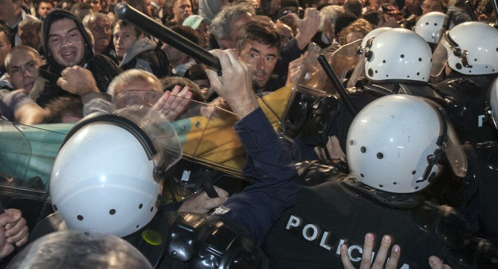 A riot policeman hits Montenegro's opposition leader Nebojsa Medojevic (facing camera, on R of baton) with a baton while dispersing protesters outside the parliament building in the capital Podgorica, Montenegro, October 17, 2015.