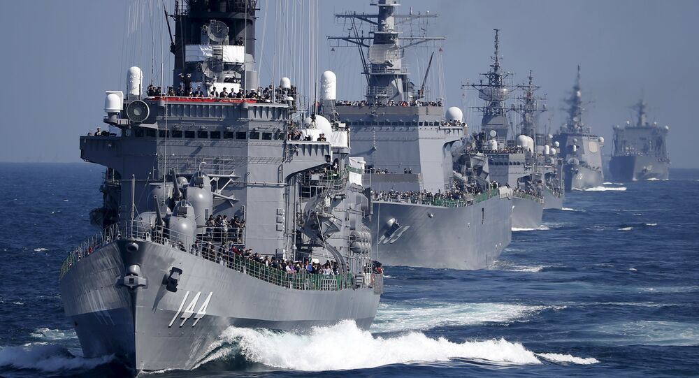 Japan Maritime Self-Defense Force (JMSDF) destroyer Kurama (L), which is carrying Japan's Prime Minister Shinzo Abe, leads the JMSDF fleet during its fleet review at Sagami Bay, off Yokosuka, south of Tokyo