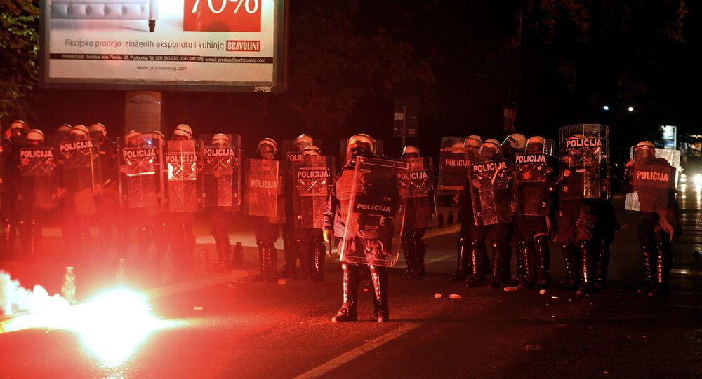 Demonstrators throwing torches at Montenegrin police officers during anti-government protest in Podgorica, Montenegro, Sunday, Oct. 18, 2015.