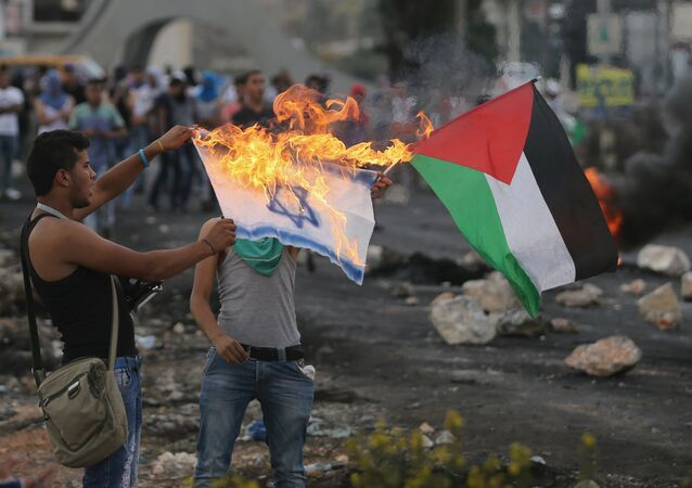 A Palestinian protester burns a replica Israeli flag as another holds a Palestinian flag during clashes with the Israeli troops near the Jewish settlement of Bet El, near the West Bank city of Ramallah October 18, 2015