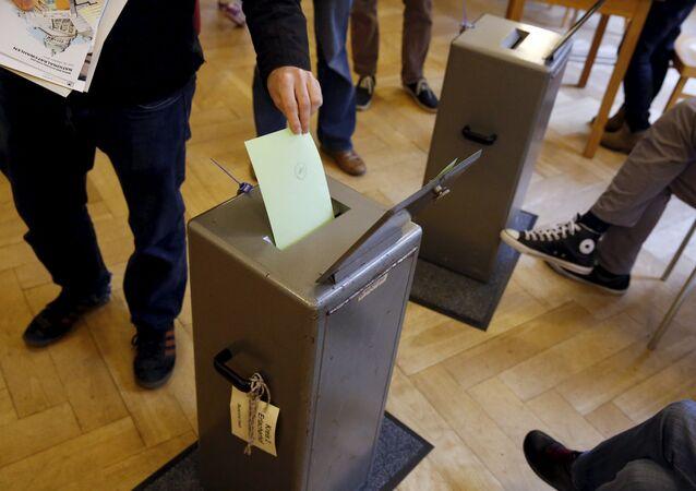 People cast their vote in a school house in Bern, Switzerland, October 18, 2015.