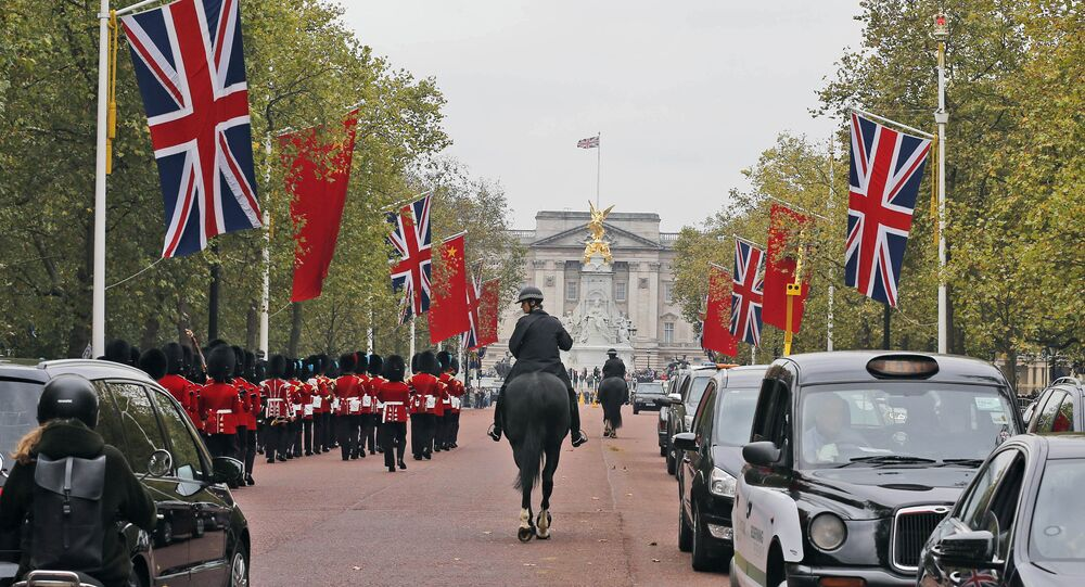 China flags are fixed on poles beside Union flags along The Mall towards Buckingham Palace in London, Friday, Oct. 16, 2015.