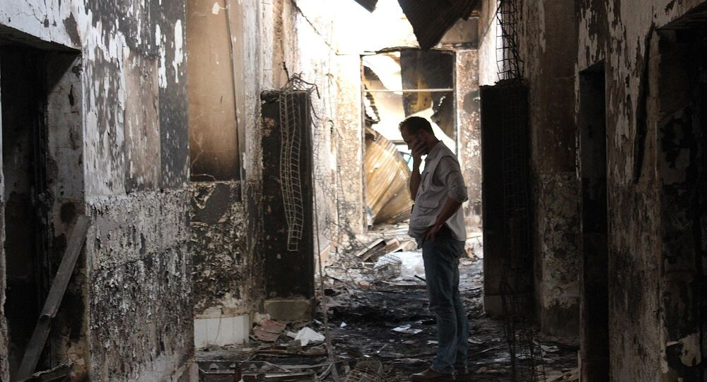 In this Friday, Oct. 16, 2015 photo, an employee of Doctors Without Borders walks inside the charred remains of their hospital after it was hit by a U.S. airstrike in Kunduz, Afghanistan.