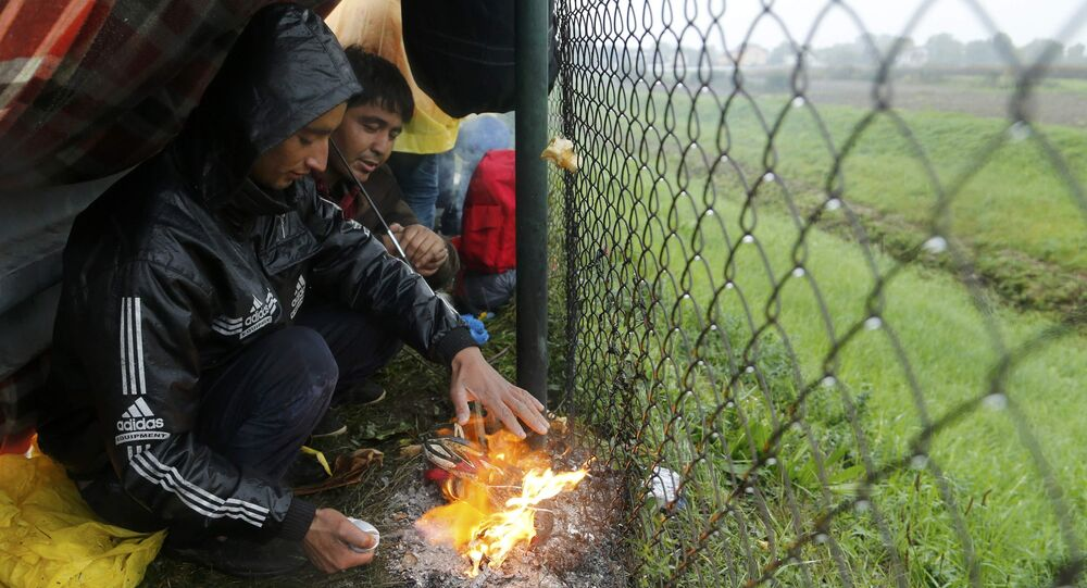 Migrants burn shoes in a bonfire to warm themselves up as they wait at the border with Slovenia in Trnovec, Croatia, October 19, 2015.