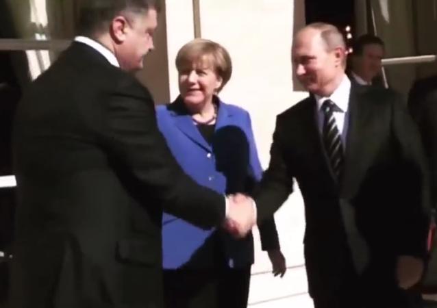 Russian President Vladimir Putin shakes hands with Ukrainian President Petro Poroshenko