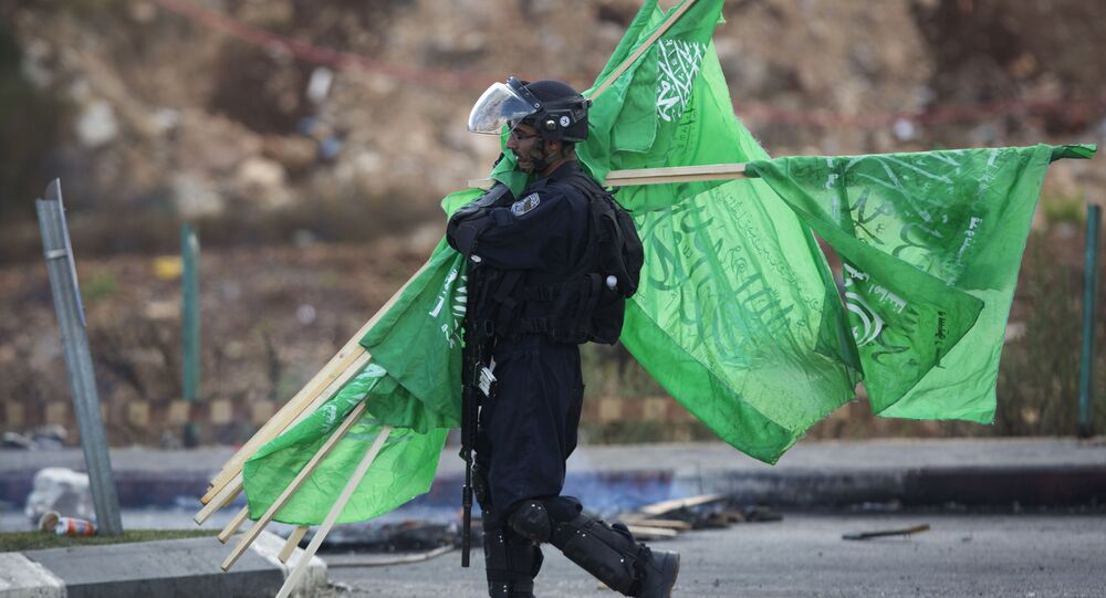 A member of the Israeli security forces carries flags of the Palestinian movement Hamas.