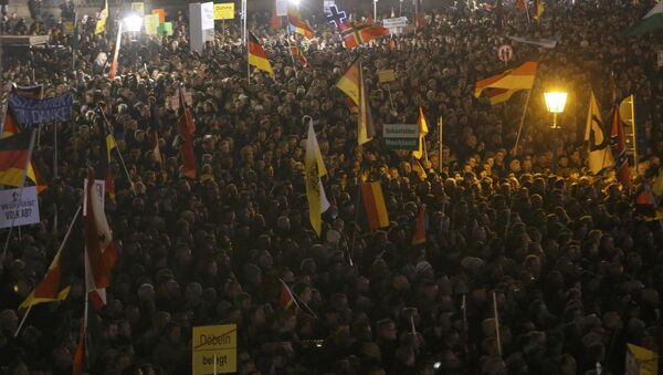 People gather for an anti-immigration demonstration organised by rightwing movement Patriotic Europeans Against the Islamisation of the West (PEGIDA) in Dresden, Germany October 19, 2015. - Sputnik International