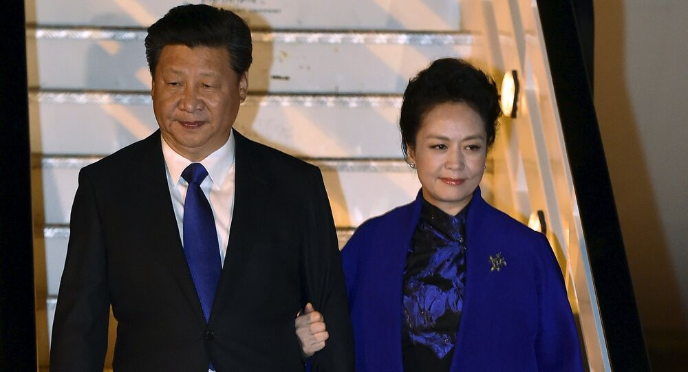 Chinese President Xi Jinping and his wife Peng Liyuan arrive for a four-day state visit at London's Heathrow Airport, October 19, 2015